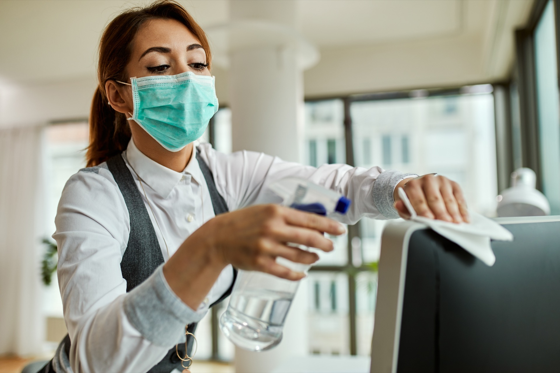 Office cleaner performing cleaning services on computer