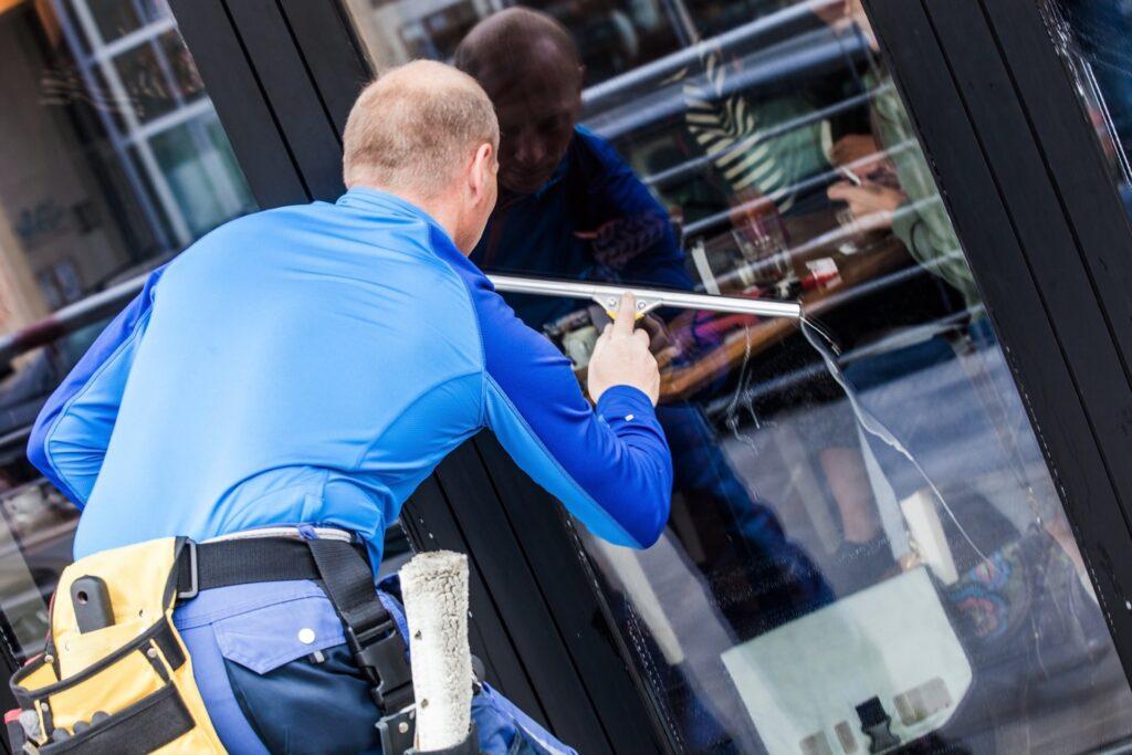 Man washing windows of business